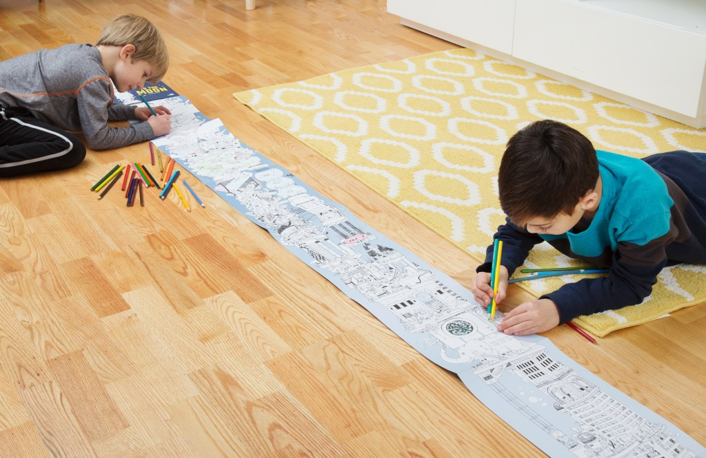 Two little boys are seen coloring on The Longest coloring book