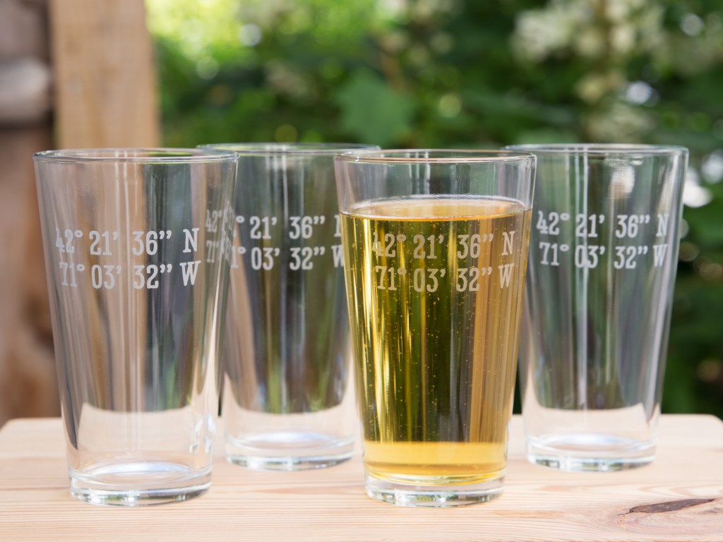 Four custom latitude & longitude pint glasses from Susquehanna Glass Company sit on a patio table