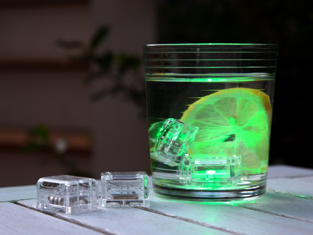 A cocktail with a lemon wheel is seen illuminated by glowing drink ice cubes from Glo Drinks
