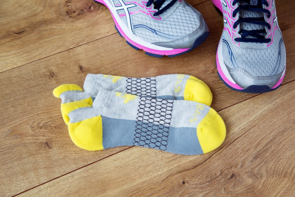A pair of yellow and gray Bombas socks lay next to a pair of gray & pink running sneakers