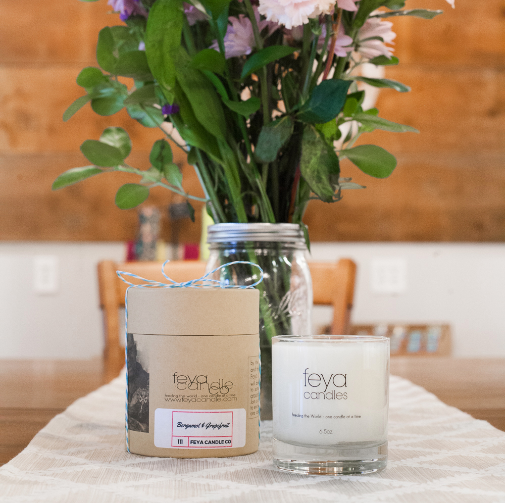 A Feya soy candle sits on a table next to a bouquet of fresh flowers