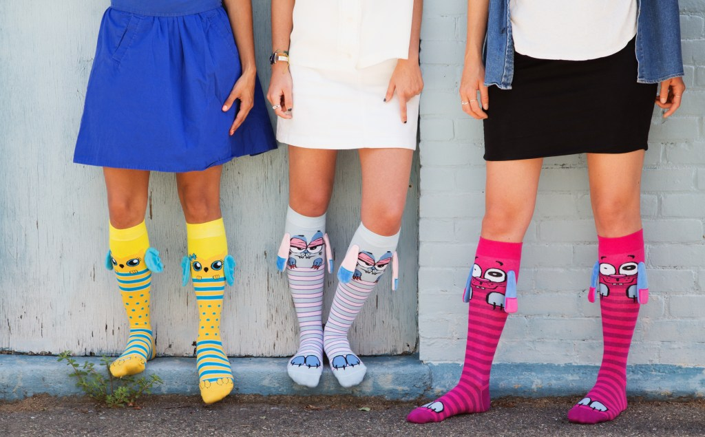 Three young girls are seen wearing colorful character knee socks from Mooshwalks