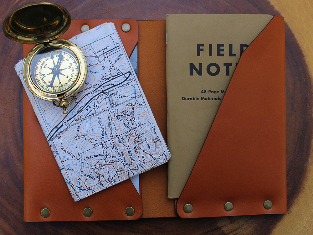 A compass, map, and field notebook are seen tucked into a leather studded journal wallet from American Bench Craft