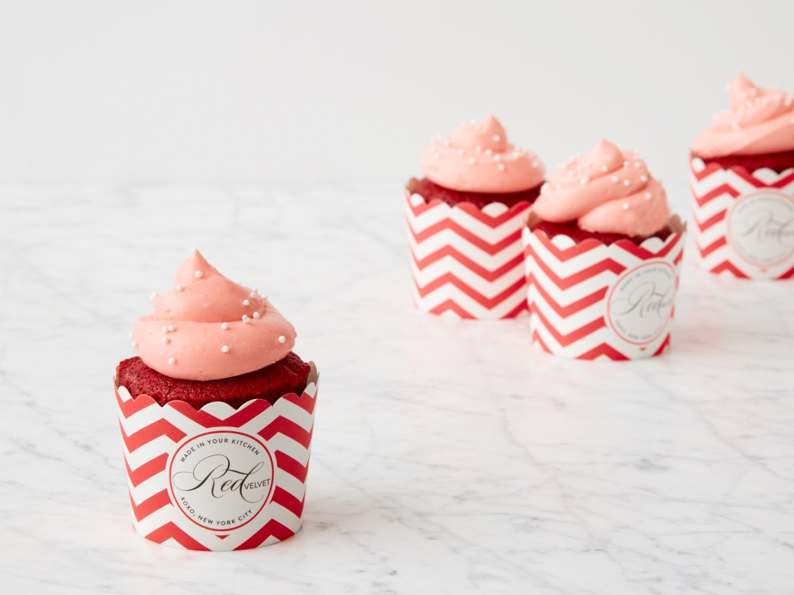 Three pretty red & pink cupcakes from Red Velvet NYC sit on a table