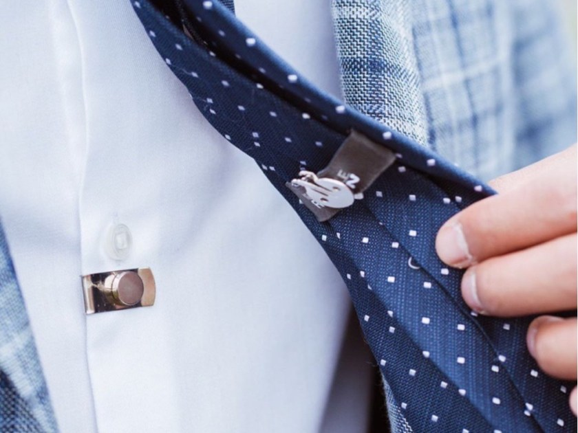Close up of a man's navy polka dot tie securing to his shirt with a CLIP OFF magnetic tie stay