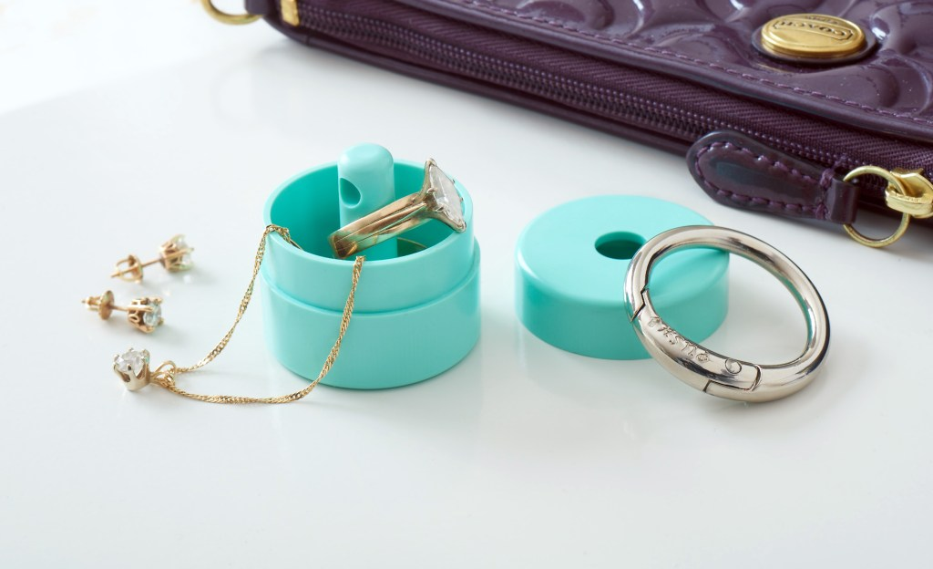A necklace, earrings and a ring are seen tucked safely in a aqua Lion Latch jewelry keyring holder