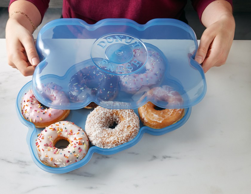 A woman is seen putting half a dozen fresh donuts in a blue donut storage container from Muffin Fresh