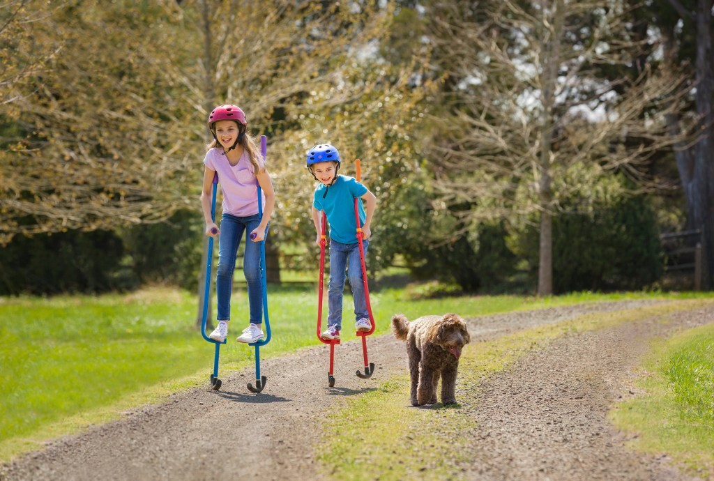 Two kids are seen walking in play stilts from Amazing Featz outdoors with their dog