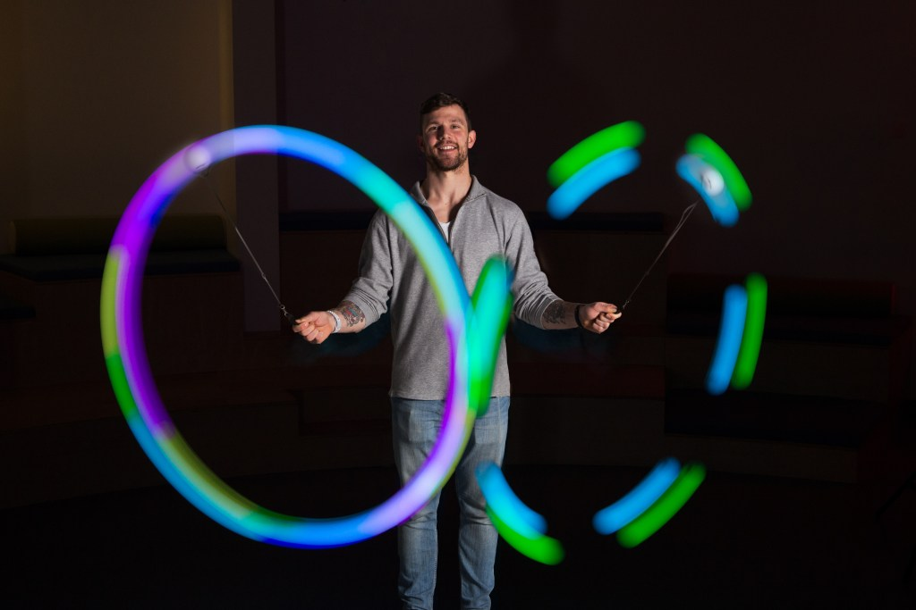 A young man is seen playing with a set of Spin Balls LED poi balls