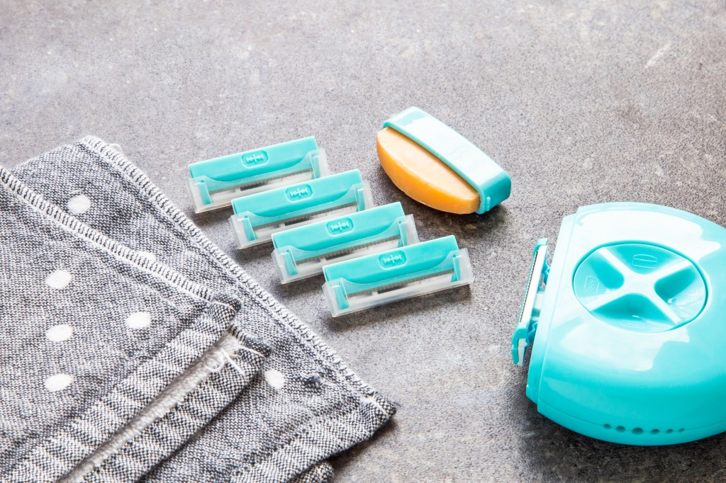 An aqua 3-in-1 portable razor from Sphynx with replacement cartridges sits on a bathroom counter