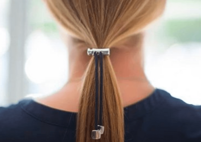 A young girl with blonde hair is seen wearing her hair in a ponytail with Pulleez metal sliding hair ties holding her hair back