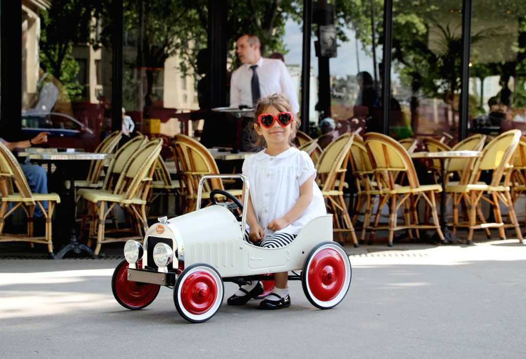 A little girl wearing heart sunglasses is seen sitting in a white Baghera classic pedal car