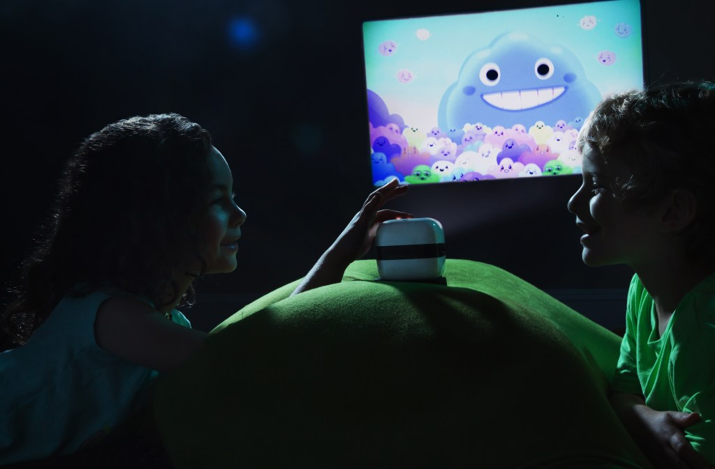 Two kids are seen using a Cinemood handheld cinema projector to play a cartoon