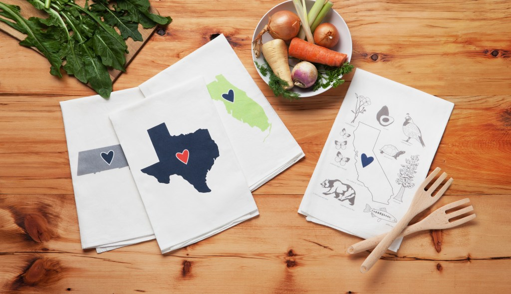 Florida, Texas & Massachusetts Love My State tea towels from Coast & Cotton sit on a butcher block