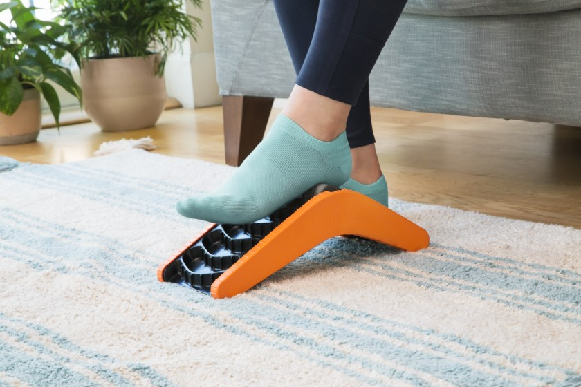 A person is seen stretching their foot using HighHealer's 5-in-1 foot stretcher in their living room