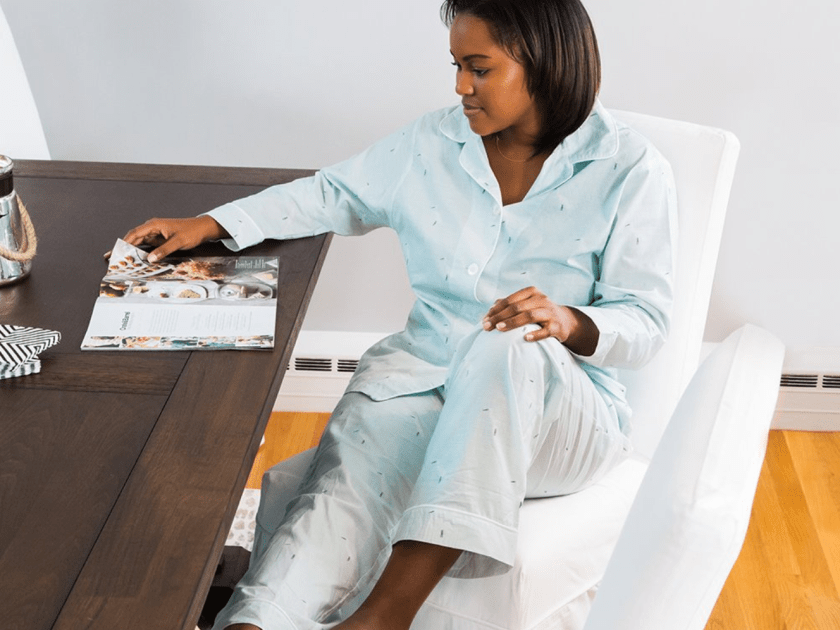 A woman sits in a chair reading a magazine wearing light blue pima cotton pajamas from The Cat's Pajamas