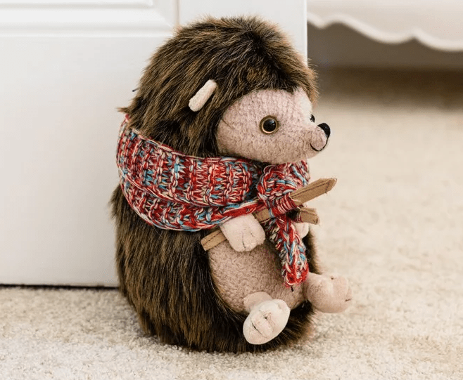 An adorable stuffed hedgehog doorstop from Dora Designs holds open a door