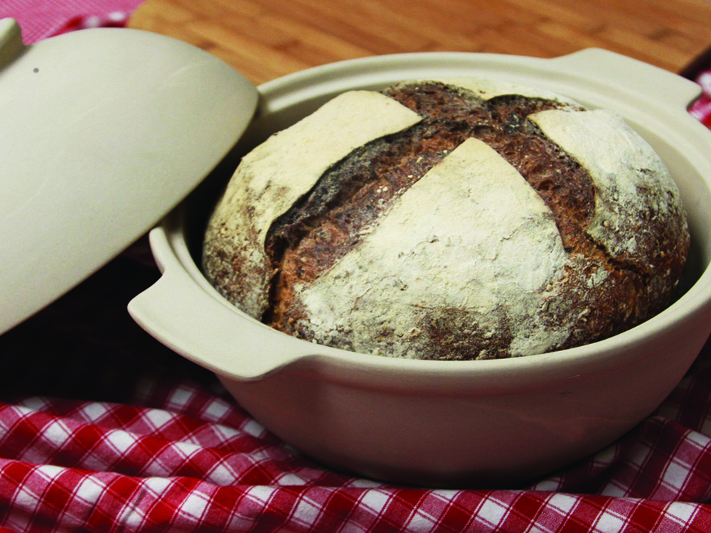 A loaf of bread sits in the Sassafras Bread Dome, a ceramic pot with a lid.