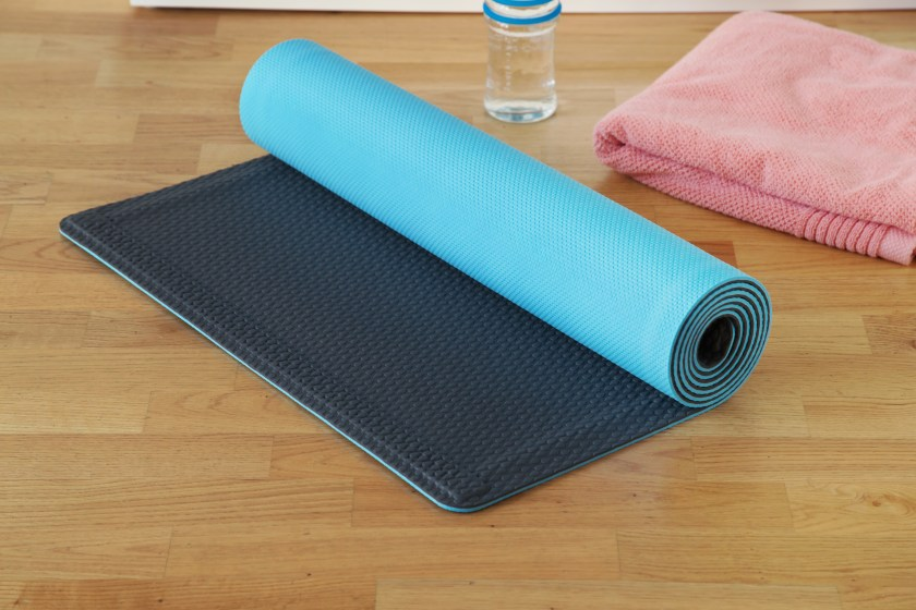 A blue and black YoYo self-rolling yoga mat lays next to a water bottle and towel