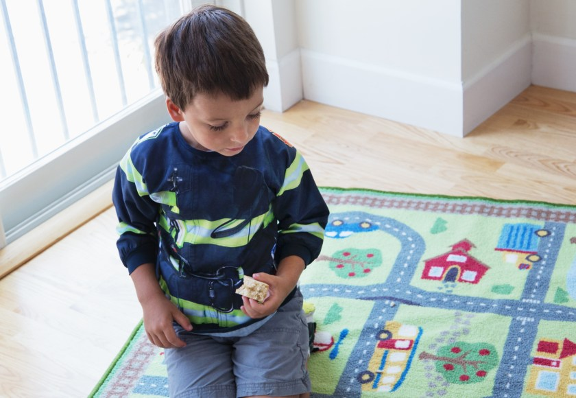 A little boy is seen playing on a town rug wearing a firefighter roleplaying bib from Mixed Pears