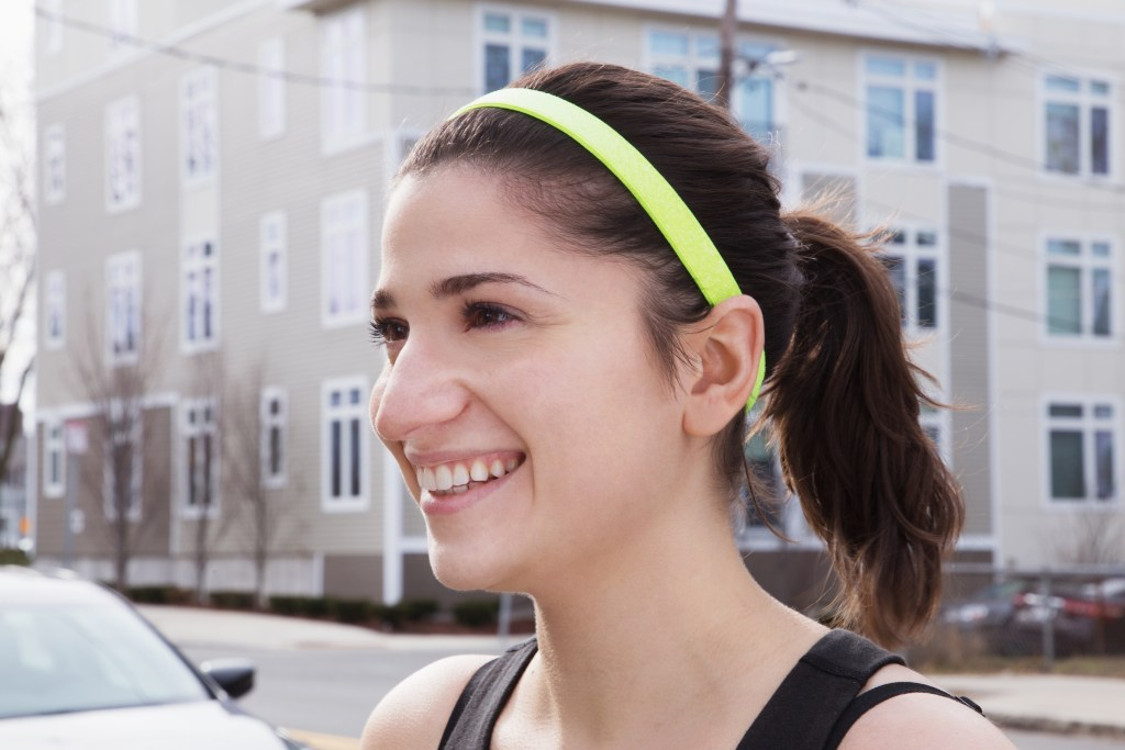 A girl is seen running wearing a sparkly neon wide no-slip headband from Sparkly Soul