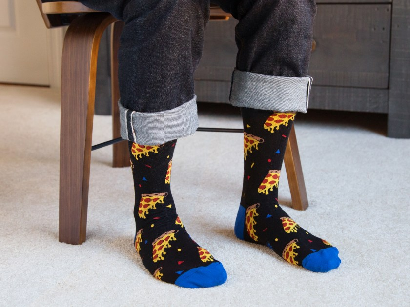 A man is seen sitting wearing a pair of pizza slice printed socks from Sock It To Me