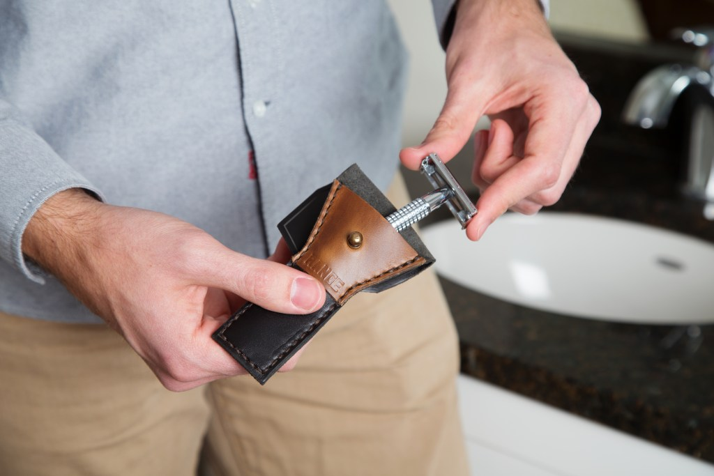 A man is seen slipping his razor into a leather safety razor case from Range Leather Co