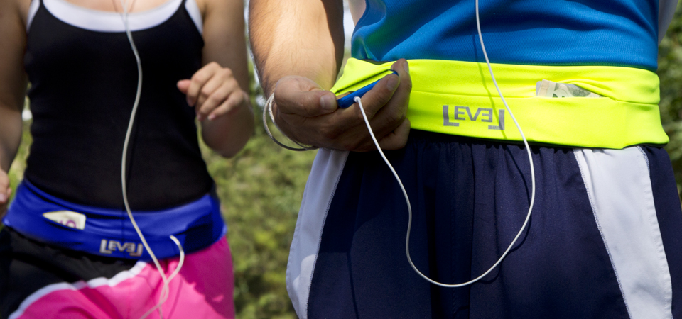 Two people are seen jogging wearing neon colored FlipBelts to hold their stuff