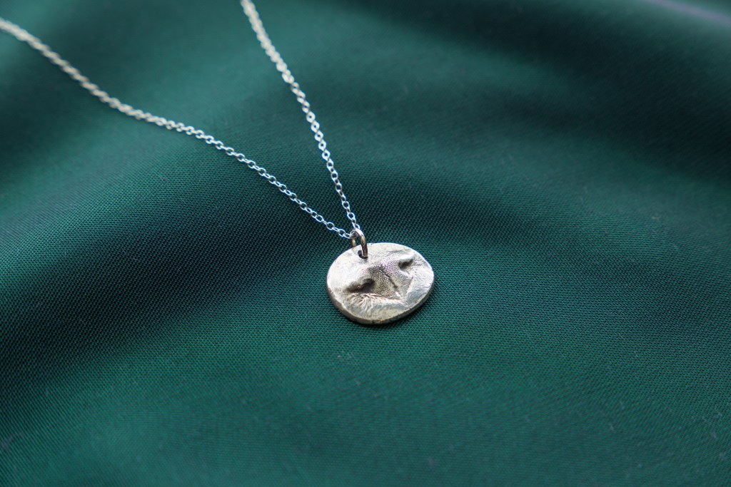 An impression of a pet's nose can be seen captured in a metal pendant necklace from Precious Metal Prints