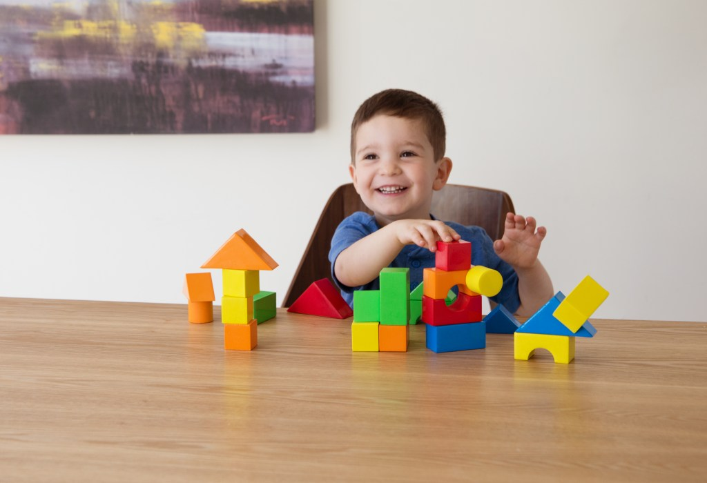 A little boy is seen playing with self-adhering building blocks from Gecko Blocks