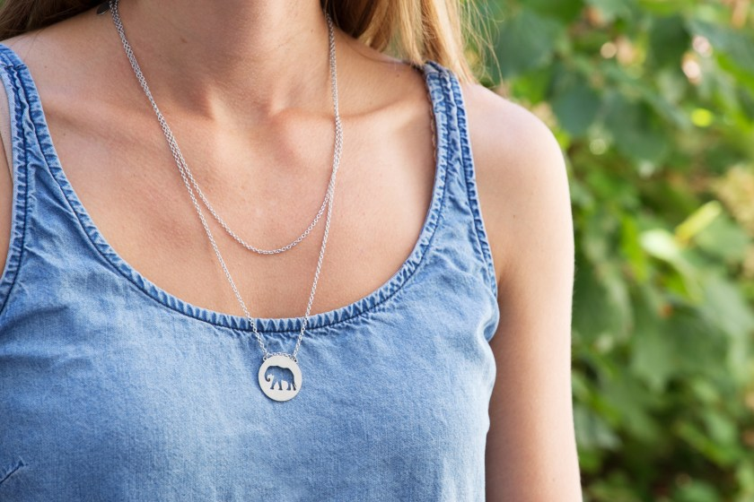 A woman wearing a blue shirt is seen with a silver elephant spirit animal necklace from Jaeci around her neck