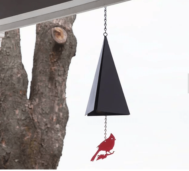 A coastal-inspired wind bell from North Country Wind Bells with a cardinal on it hangs from a porch