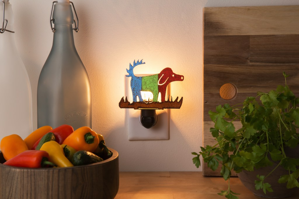 A recycled metal nightlight of a dog from Whimsies is seen plugged into a wall