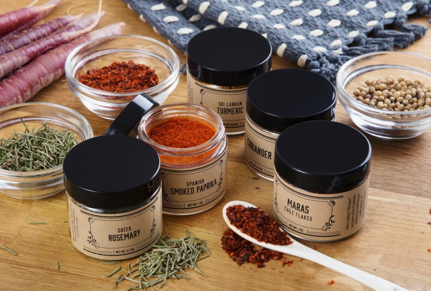 Rosemary, Smoked Paprika, Madras Chili Flakes, Coriander & Tumeric spice jars from Curio Spice Co are seen on a table
