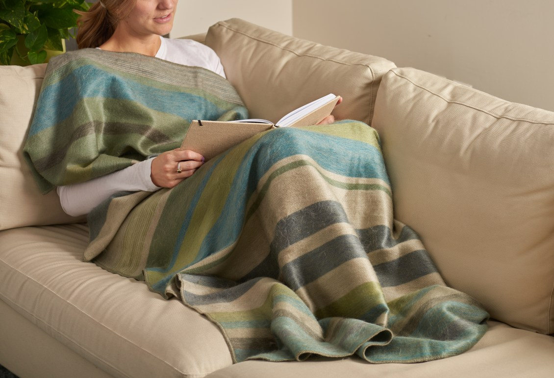 A woman is seen reading on the couch covered in a blue, green & beige Shupaca brushed alpaca throw