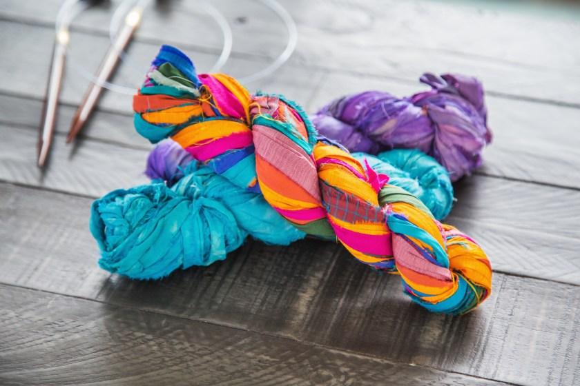 Three bundles of upcycled sari silk ribbon yarn from Darn Good Yarn sit on a table