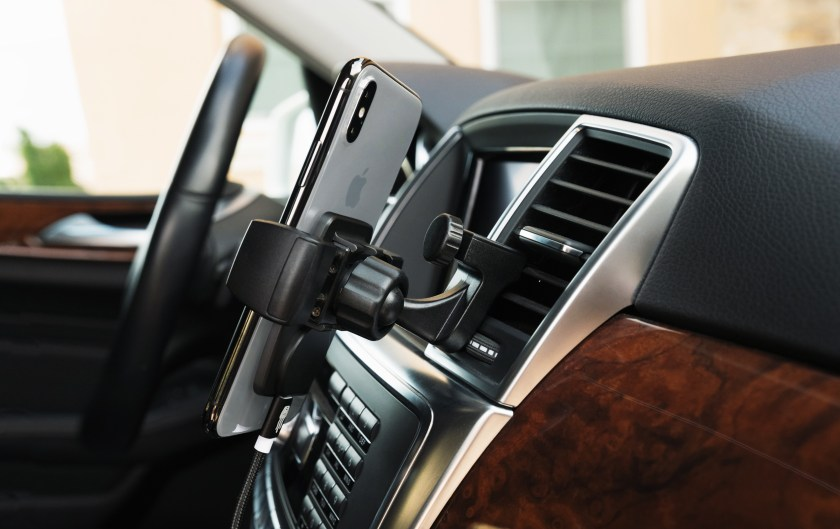 An iPhone is seen mounted to a car vent using Square Jellyfish's car vent phone mount
