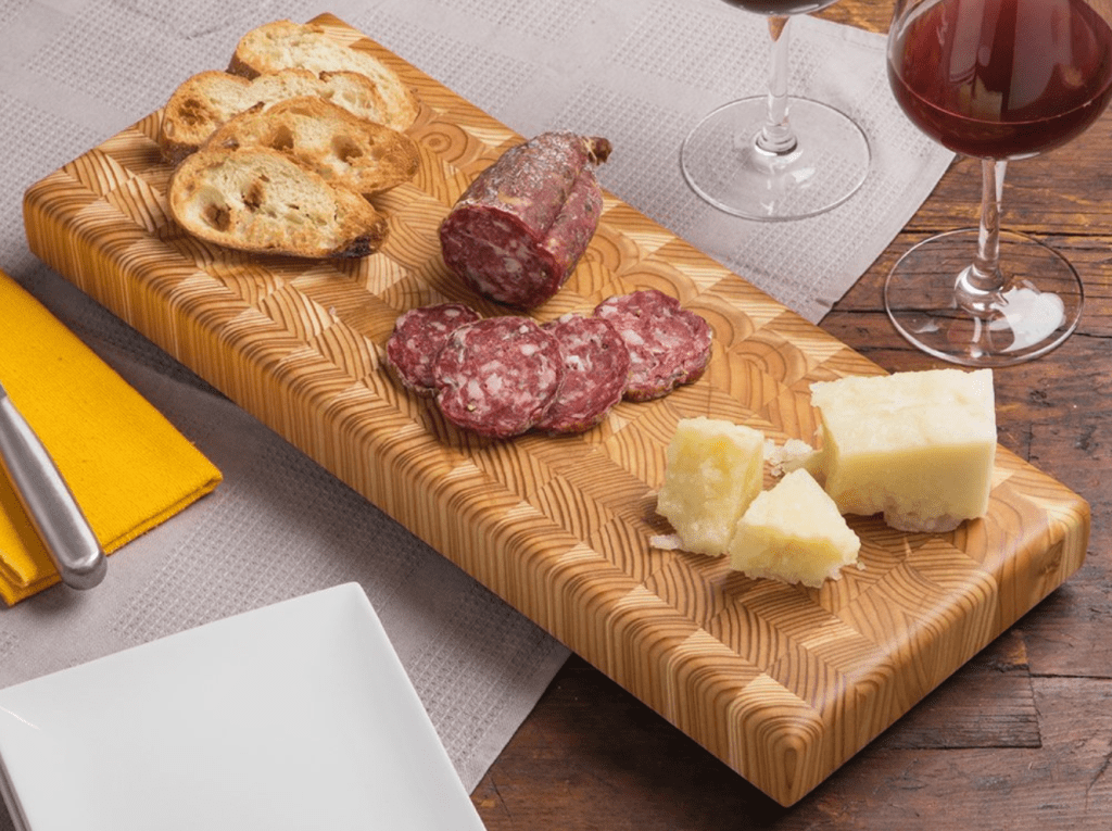 Charcuterie are sliced on an end grain double cheese board from Larch Wood