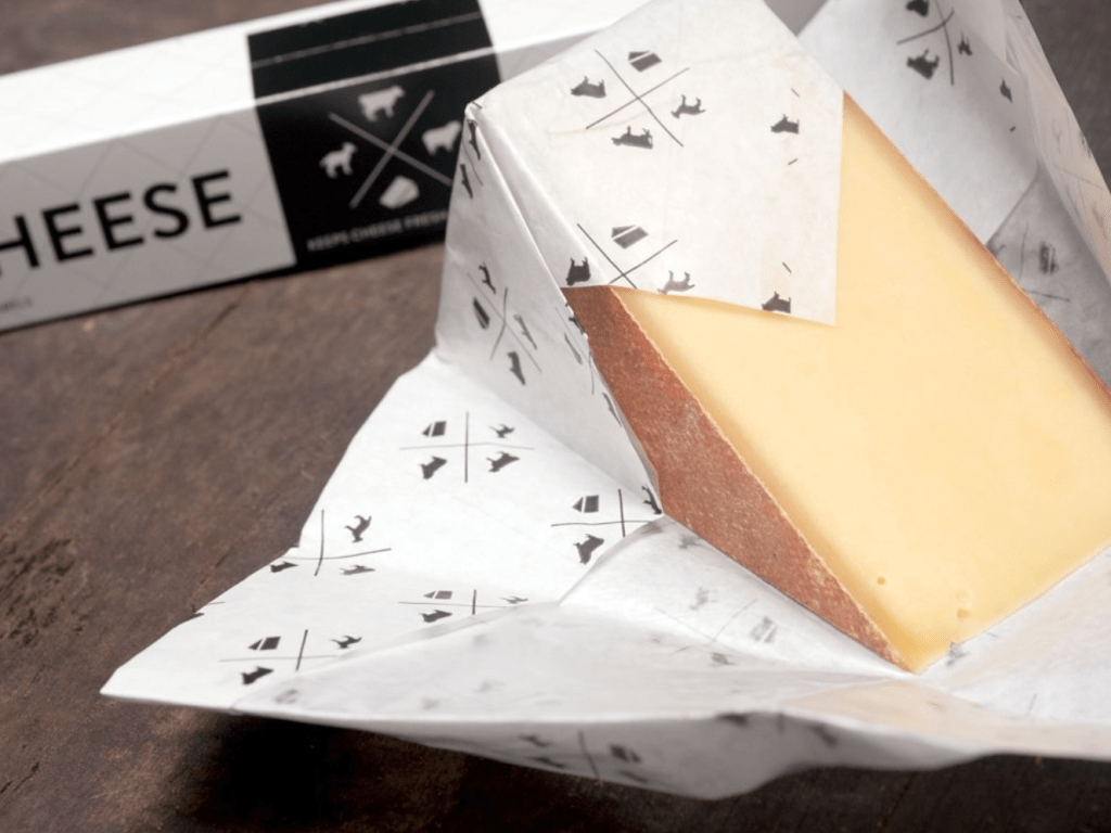 A wedge of cheese is seen wrapped in Formaticum cheese storage papers