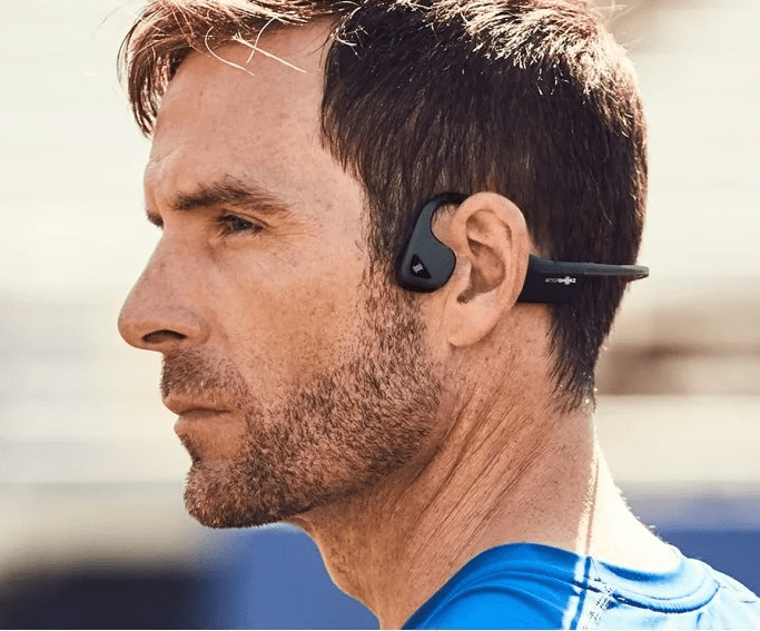 A man in a blue shirt is seen wearing a pair of black Trez Air headphones by Aftershokz
