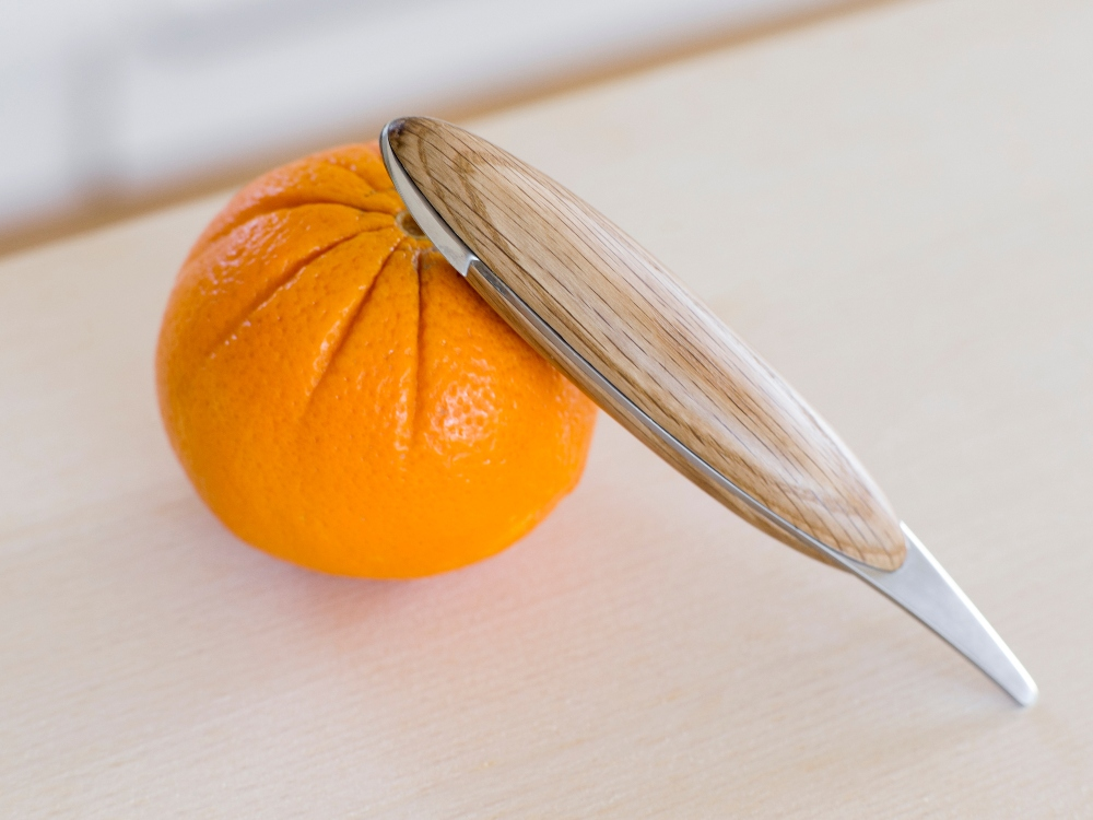 Spring Copenhagen's wooden minimalistic orange peeler rests on an orange