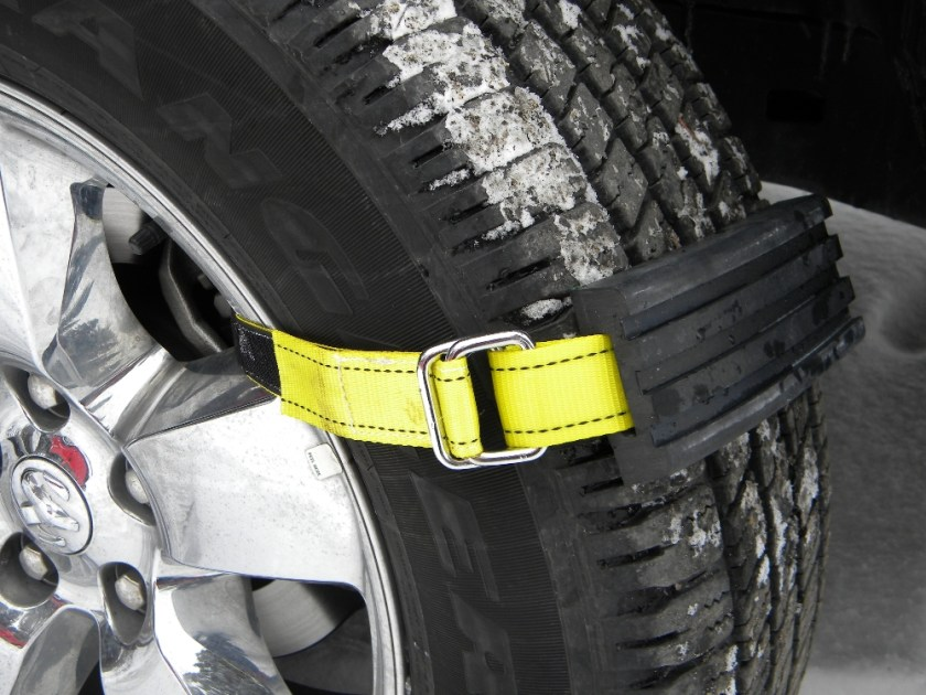 Neon yellow tire traction straps from TRAC-GRABBER are seen strapped to an icy tire