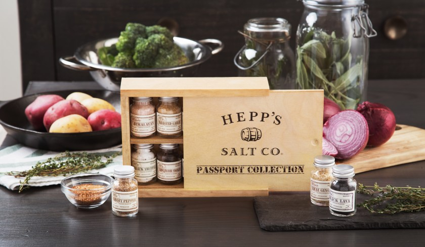 Surrounded by fresh cooking ingredients is a gift box of Hepp Salt Co.'s Passport collection of finishing salts