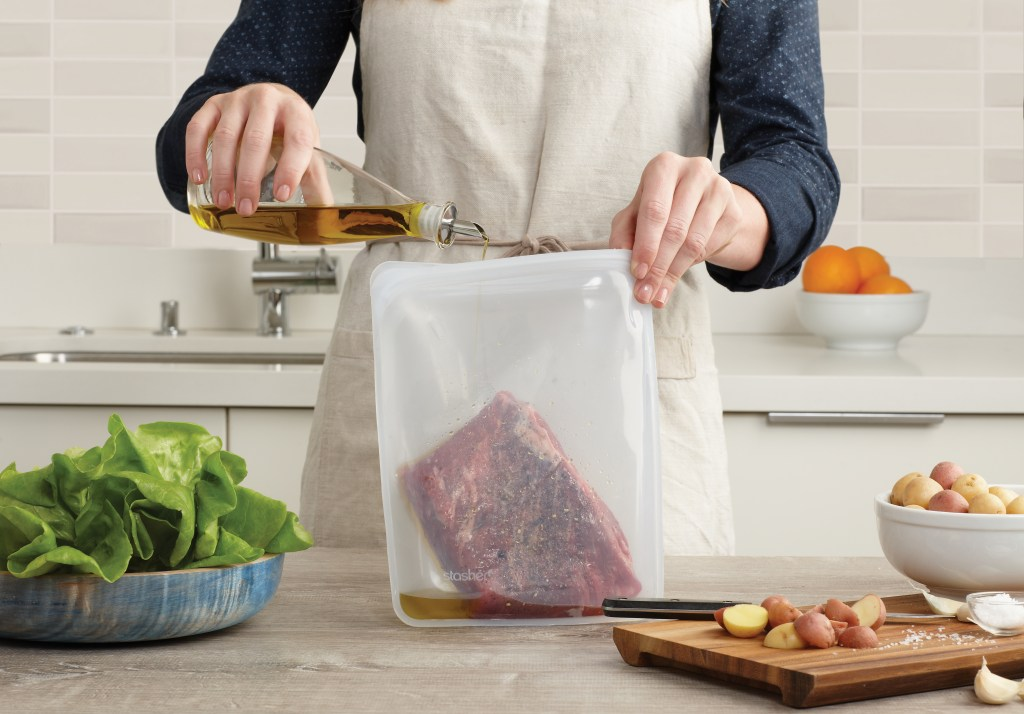 A man is seen marinating a steak in a Stasher half gallon silicone bag