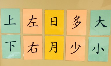 "Hanging on the main wall in the language classroom, these are ""opposites"" signs. From left, up/top and down/bottom, left and right, sun and moon, more and less, and big and small."