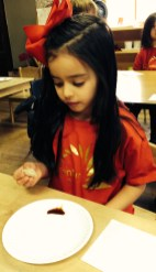 This primary student resplendent in Chinese New Year finery dips her zhēngjiǎo in soy sauce. Yum!