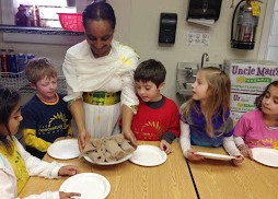 Wearing habesha kemis, Ms. Kipnesh instructs the children on how to prepare there enjera pancakes.