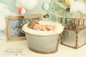 baby-asleep-in-basket-at-professional-photo-studio-on-hot-air-balloon-travel-inspired-set
