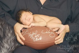 baby-asleep-on-top-of-a-football-dads-hands-holding