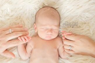 parents-hands-holding-newborn-boy